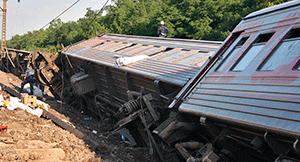 Сбившиеся в кучу вагоны поезда лежат рядом с рельсами, колесами вверх