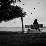 Грустные звуки — девушка одиноко сидит на сером фоне моря под порывом ветра
