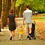 Звук городского парка слушает молодая семья, прогуливающаяся по дорожкам парка