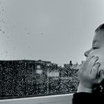 Мальчик смотрит в окно и слушает звуки дождя за окном