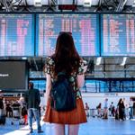Звуки аэропорта скачать — девушка стоит перед табло с расписанием самолетов