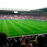 Звуки футбола — на фото футбольное поле с игроками на стадионе с трибунами